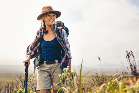 Smiling woman hiking in the countryside wearing backpack. Senior woman walking on a hill holding a trekking pole.