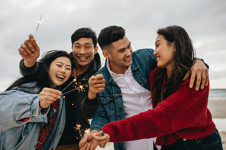 Diverse group of young people celebrating new year's day at the beach. Young asian people having fun with sparklers outdoors at the sea shore.