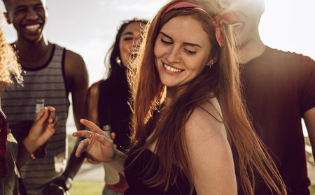 Beautiful woman dancing with friends around outdoors. Woman having a great time with group of friends on summer day.