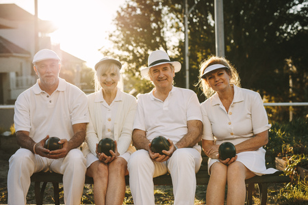 Cheerful senior men and women sitting together on in a park with boules in hand. Senior friends sitting together on a bench in a park. Stock Photo