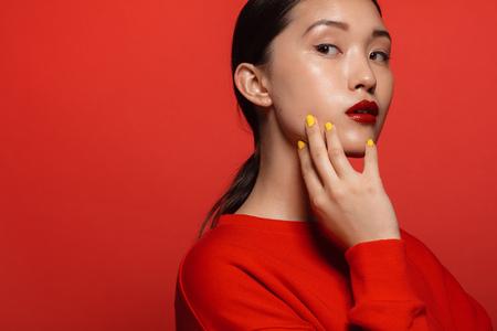 Il ritratto di giovane donna asiatica attraente con bello compone su fondo rosso. Modello femminile asiatico con top rosso e rossetto. Archivio Fotografico