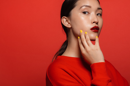 Portrait of attractive young asian woman with beautiful make up on red background. Asian female model with red top and lipstick.
