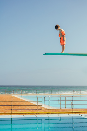 Boy with sleeve floats standing on high spring board and looking at swimming pool below. Boy learning to dive from diving platform at outdoor swimming pool. Stockfoto