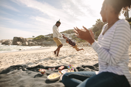 Father circling his son on the beach with mother clapping hands. Happy family enjoying themselves on the beach. Stock Photo