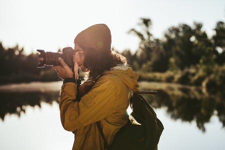 Tourist taking a photo using a dslr camera. Side view of a traveler looking into his digital camera to take a photo.