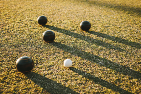Close up of boules with their long shadows on the ground. Four black boules lying near a jack in a park. Stockfoto