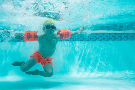 Underwater shot of a boy with sleeve floats in the pool. Child learning to swim in a swimming pool. Banco de Imagens