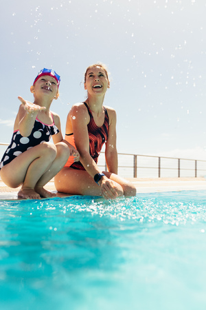 Smiling child with swimming coach sitting on pool edge after swimming lessons. Girl sitting on swimming pool edge with her trainer having fun.