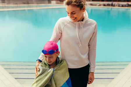 Girl wrapped in towel standing with a woman by the pool. Girl child with coach at swimming pool.