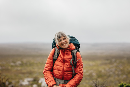 Close up of a senior woman standing on a hill wearing jacket and backpack. Smiling senior woman on a hiking trip on a hill. Stock fotó - 119039765
