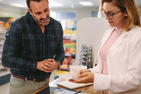 Apothekerin, die eine Medizinbox hält und den Kunden in der Apotheke berät. Apotheker schlägt dem Käufer in der Apotheke ein Medikament vor.