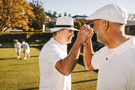 Senior men giving high five celebrating success. Elderly people enjoying a game of boules in a park. Stock Photo