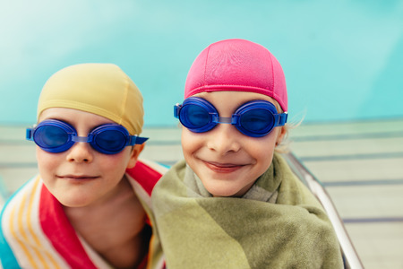 Boy and girl in swimming goggles and cap wrapped in towel after swimming training. Two kids wrapped in towel by poolside. Stock fotó