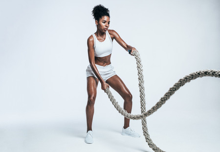Fitness woman using training ropes for exercises. Athlete working out with battle ropes on white background.