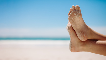 Close up of feet of a person relaxing at a peaceful beach on a sunny day. Legs of a person at a beach in a relaxed position with one leg over the other.