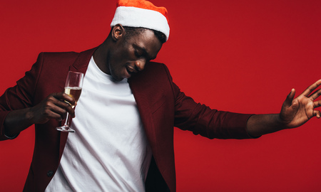 African man wearing santa hat with champagne dancing against red background. Happy young black guy enjoying at christmas party.