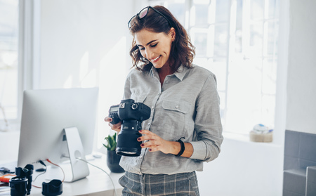 Female photographer checking pictures on camera and smiling. Caucasian woman in casuals standing in her office looking at the photos on her dslr camera. Stockfoto