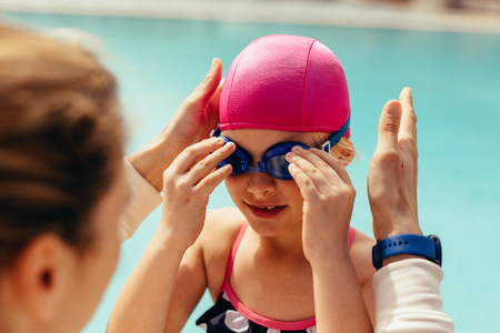 Girl wearing swimming goggles by poolside with female coach in front. Girl getting ready for her swimming class. Reklamní fotografie