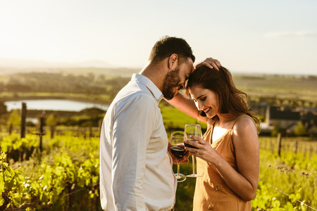 Couple on a romantic date standing together drinking red wine in a wine farm. Couple on a wine date spending time together. Stock Photo