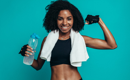 Young fitness woman flexing muscles and smiling. African female model in sportswear holding a water bottle and towel around her neck showing her muscles.