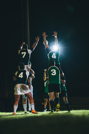 Rugby players jumping for line out at the stadium. Teams jumping for possession of the ball during rugby match. 版權商用圖片