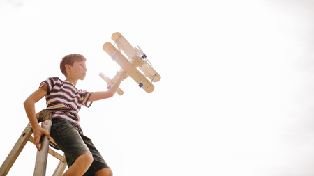 Boy sitting on top of a ladder with toy airplane against bright sunlight. Boy imagining to be pilot, flying a top aeroplane.