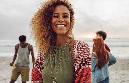 Jolie femme africaine sur la plage souriant à la caméra. Jolie jeune femme debout à la plage avec un groupe d'amis en arrière-plan. Banque d'images