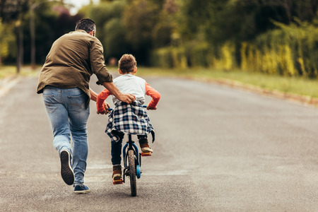 Rear view of a boy riding a bicycle while his father runs along holding the kid. Father teaching his son to ride a bicycle. Foto de archivo