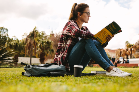 Side view of young woman sitting outdoors at college campus reading a book. Female student reading a book at university campus. Standard-Bild