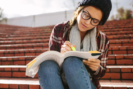 Female student using marker pen to highlight text in a book. Woman student sitting on steps at campus and studying.