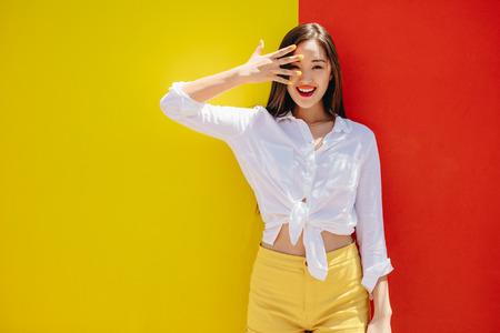 Lächelndes asiatisches Mädchen, das gegen einen bunten Hintergrund steht. Fröhliches Mädchen in bunten Kleidern, das draußen mit der Hand zum Gesicht steht.