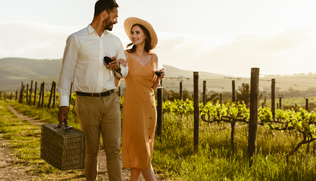 Smiling couple walking in a wine farm drinking red wine and carrying a picnic basket. Couple in love on a date walking in a vineyard holding each other. Imagens