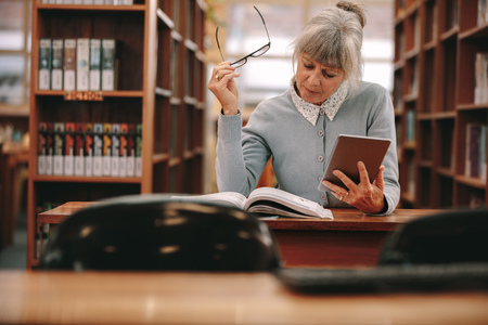 Senior woman using a tablet pc for reference while reading a book in library. Woman sitting in a library reading a book.