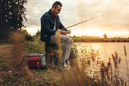 Man sitting on a tree trunk beside a lake with his fishing rod. Man enjoying his leisure time fishing in a lake.