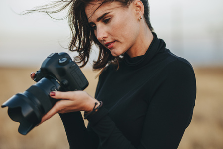 Photographer checking pictures on dslr camera. Young woman wearing casuals standing outdoors with professional camera.