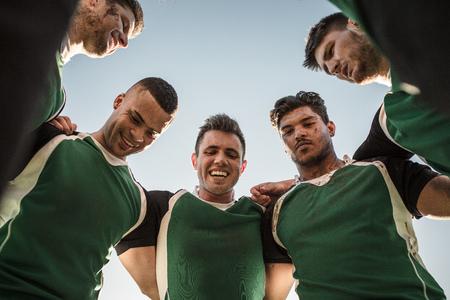 Inquadratura dal basso dei giocatori di rugby in piedi contro il cielo limpido. Squadra di rugby in huddle dopo la partita.