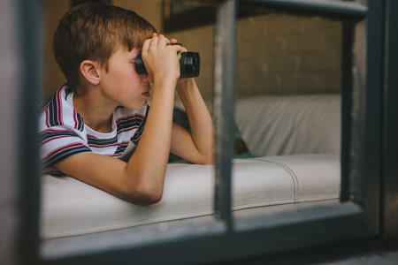 Curious boy looking out the window with binocular. Small boy on sofa looking outside window using binoculars.