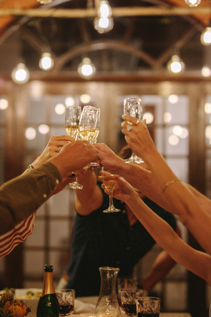 Hands of young people toasting drinks at a party. Young friends having drinks to celebrate a special occasion.