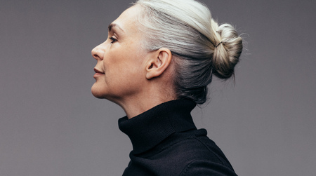 Side view of senior woman on gray background. Profile view of mature woman in black casuals. Reklamní fotografie