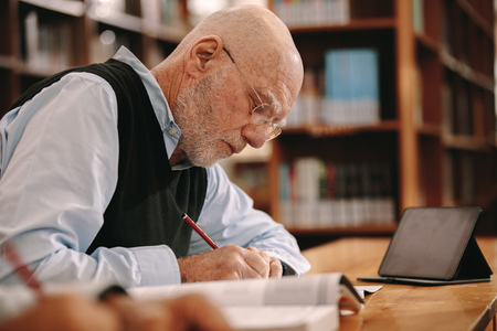 Senior man sitting in classroom with a tablet pc on the table and making notes. Elderly man writing in his book sitting in a library. Banque d'images