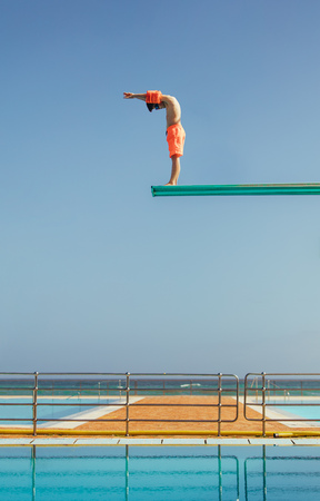 El muchacho se encuentra en una plataforma de buceo a punto de sumergirse en la piscina. Niño de pie en trampolín de buceo alto preparándose para bucear. Foto de archivo