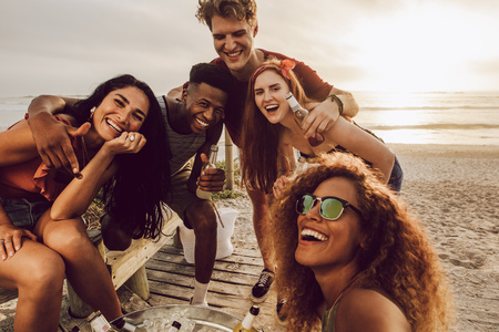 Young woman talking selfie with diverse group of friends at the beach. Multiracial young men and women posing for a selfie.