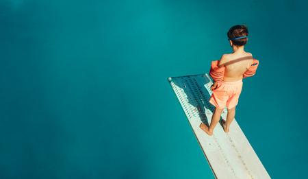Blick von oben auf den Jungen, der auf dem Sprungbrett steht und an einem Sommertag während des Schwimmunterrichts tauchen lernt. Junge, der Schwimmen im Freibad lernt. Standard-Bild