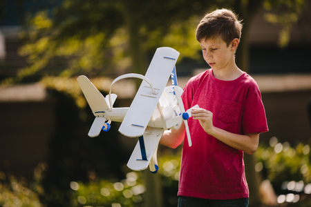 Boy playing with a toy plane outdoors. Preteen boy looking at the toy plane in his hands outdoors. Фото со стока