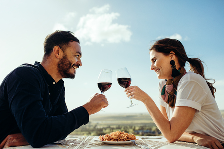 Side view of a couple sitting in an open air restaurant drinking red wine. Smiling couple toasting wine sitting at a restaurant.