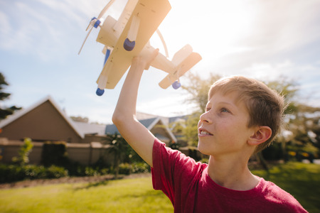 Happy boy playing with airplane toy outdoors. Boy dreams to be a pilot one day and play with airplane.