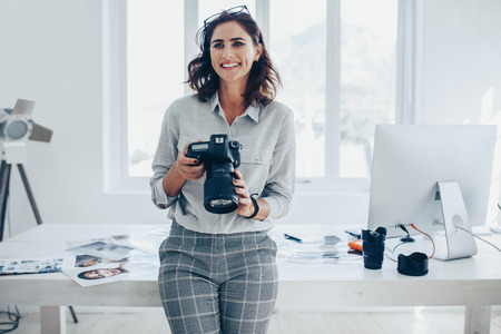 Young woman photographer with a professional camera in office. Woman photographer with digital camera.