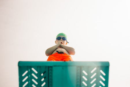 Low angle view of boy in swimming trunks, swim goggles and swimming cap standing on diving board against bright sky. Boy on diving platform at pool. 版權商用圖片