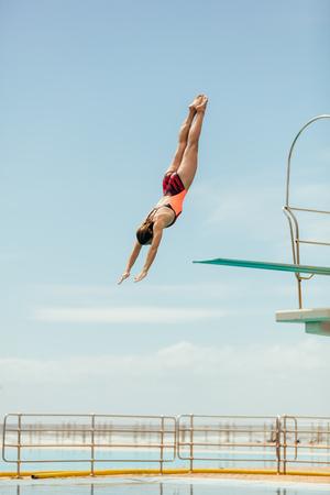 Vrouw duikt in het zwembad vanaf springplank. Vrouwelijke duiker duikt ondersteboven in het zwembad. Stockfoto
