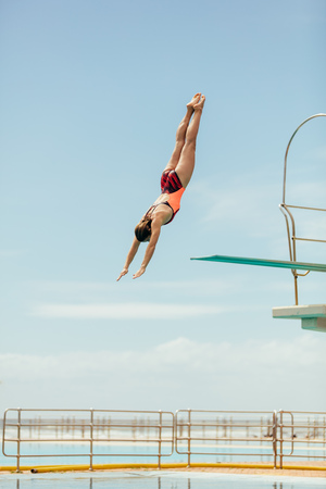 Woman diving into the pool from spring board. Female diver diving upside down into the swimming pool.